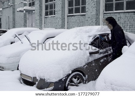 Cars after a snowfall. Windshield wiper raised up. - stock photo