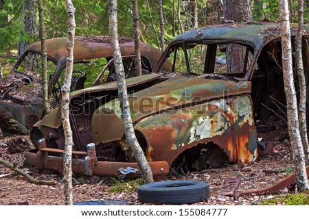 Cars at a junkyard in the woods - stock photo