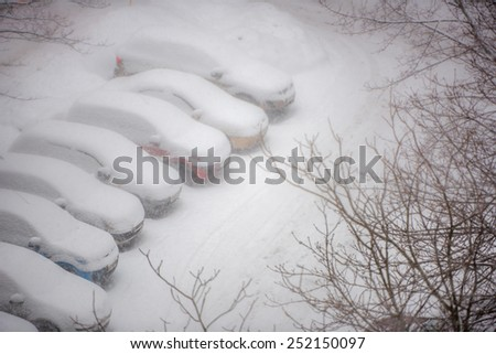 Cars covered in snow on a parking lot in the residential area during snowfall. Horizontal shot - stock photo