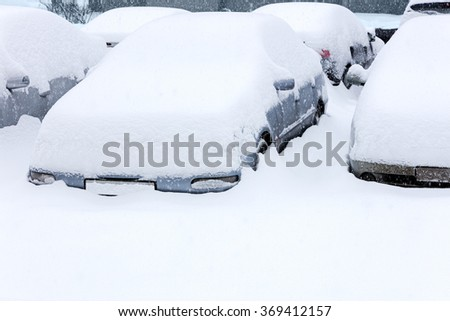 cars covered with snow in the parking lot during winter blizzard - stock photo
