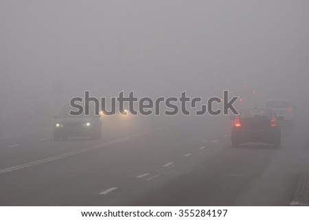 Cars in the fog. Bad winter weather and dangerous automobile traffic on the road. Light vehicles in fog. - stock photo
