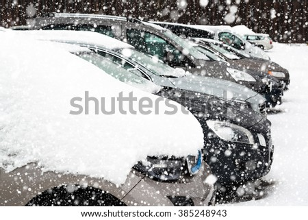 Cars on a parking lot in the winter and it is snowing - stock photo