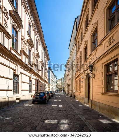 Cars parked near houses in street in Krakow, Poland, Europe. Empty lane in morning. Blue sky and good weather for tourists. - stock photo