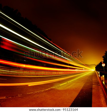 Cars pass on a country road at night - stock photo