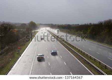 Cars passing by on rainy highway - stock photo
