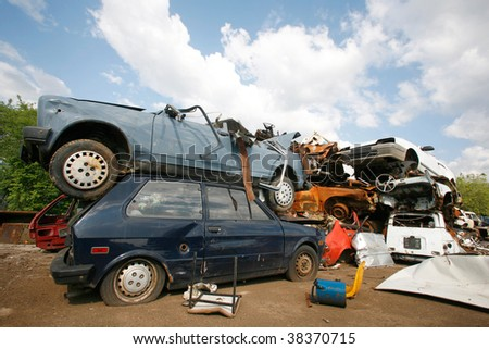 Cars piled on top of each other in junkyard - stock photo