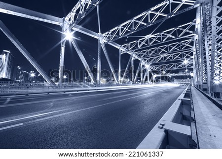cars run fast through the colorful steel bridge with long tail at night - stock photo