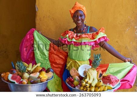 CARTAGENA DE INDIAS, COLOMBIA - JANUARY 28, 2015: Woman in traditional costume selling fruit in the historic walled city of Cartagena de Indias in Colombia - stock photo