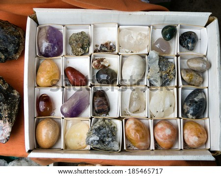 Carton box with different natural gemstones  - stock photo