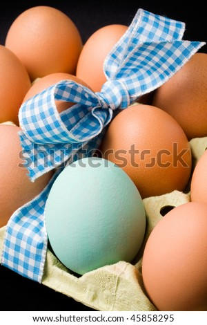 carton with brown eggs with ribbon. one is different. vertical. black background - stock photo
