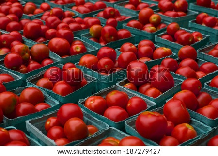 Cartons of bright red Tomatoes on display at farmers market - stock photo