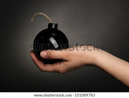 Cartoon style bomb in hand on black background - stock photo