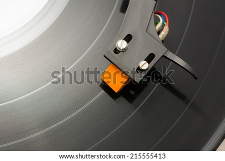 Cartridge moving on black vinyl. - stock photo