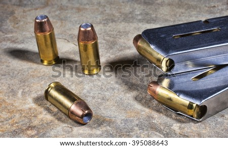 Cartridges with hollow point bullets for a handgun with magazines - stock photo