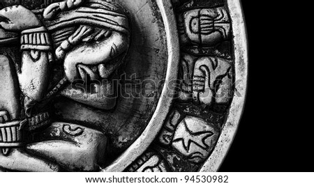 carved glyphs on a stone Mayan calendar - stock photo