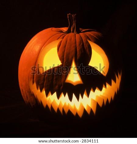 Carved Halloween pumpkin glowing in the dark. - stock photo