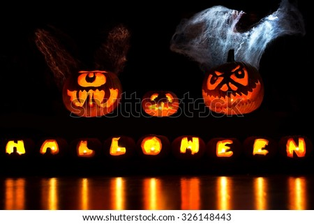 Carved Halloween Pumpkins hover over a Halloween inscription - stock photo