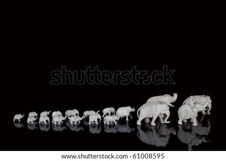Carved ivory miniature elephants lined up - stock photo