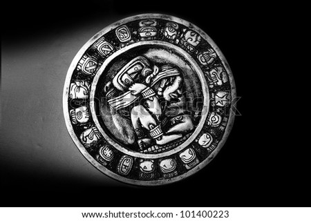 Carved Mayan calendar in dramatic light - stock photo