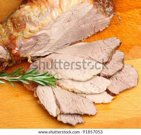Carved roast leg of lamb on wooden board. - stock photo