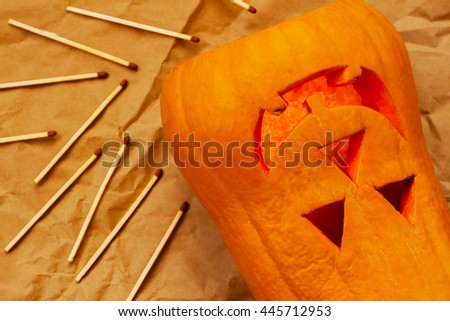 Carved smiling Scary Halloween pumpkin and matches - stock photo