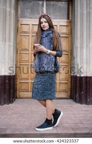 carven girl in a wreath on the street with a phone - stock photo