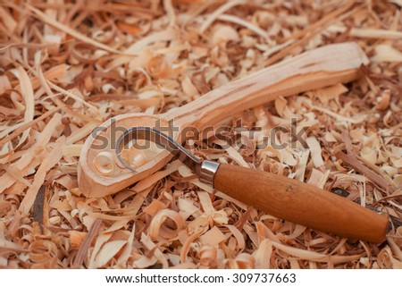 carving of a wooden spoon on wooden shavings background - stock photo