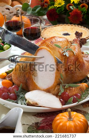 Carving roasted turkey on a server tray garnished with fresh figs, grape, kumquat, and herbs on fall harvest table. Red wine, side dishes, pie, and gravy. Decoraded with mini pumpkins  - stock photo