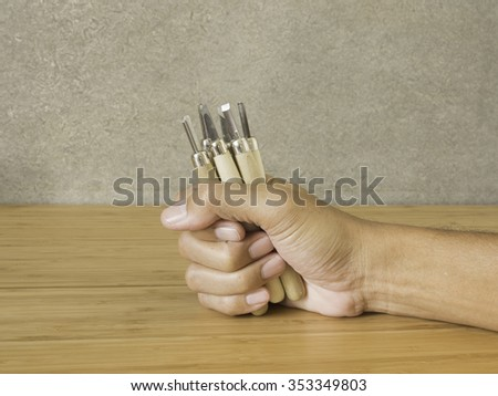 Carving tools in hand - stock photo