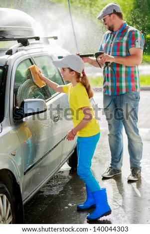 Carwash-young girl with father in carwash. - stock photo