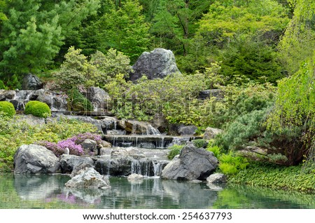 Cascade falls over rocks and green grass - stock photo
