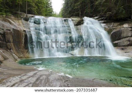 Cascading waterfall in deep forest - stock photo