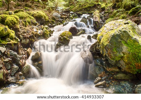 Cascading waterfall, long exposure of water flowing down mountainside into creek - stock photo