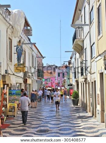CASCAIS, PORTUGAL - SEPTEMBER 13, 2013 : People walk on old town street. Cascais is popular tourist destination near city of Lisbon - stock photo