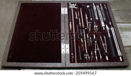 Case of drawing instruments. Old Case of drawing instruments laying on a wooden grunge table. - stock photo