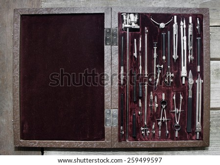 Case of drawing instruments. Old Case of drawing instruments laying on a wooden grunge table upper view. - stock photo