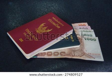 Cash and Thai passport on blue background - stock photo