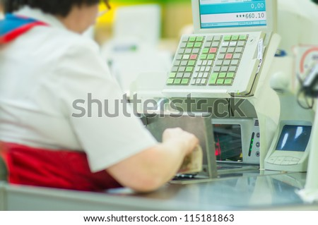Cash-desk with cashier and terminal in supermarket. Serve customer, holding money in hand - stock photo