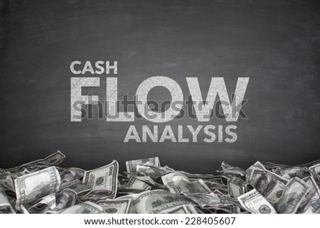 Cash flow analysis on black blackboard with dollar bills - stock photo