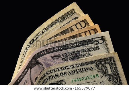 Cash in a black wallet/US Currency/American currency spread out showing various denominations  - stock photo