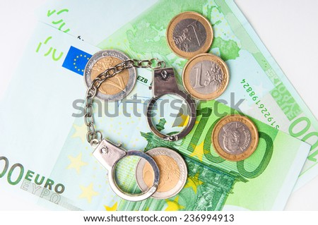 Cash money and handcuffs - stock photo
