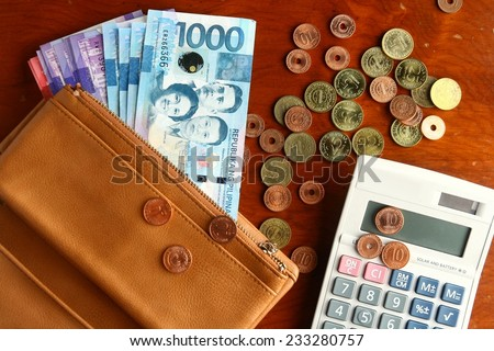 Cash money in a leather wallet, coins and a calculator Photo of a bunch of cash money in a leather wallet, coins and a calculator - stock photo