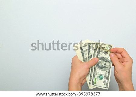 Cash US dollars in the hands on a light background. - stock photo