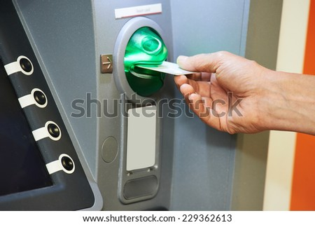 Cash withdrawal. hand inserting plastic card into the ATM - stock photo