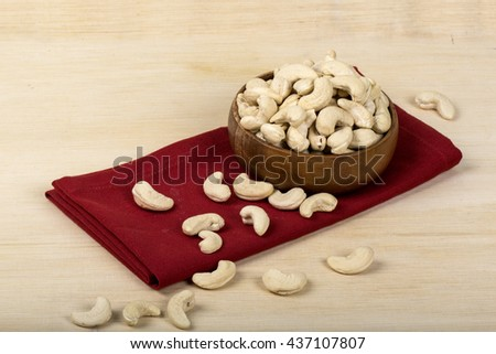 Cashew nuts in bowl on wood table - stock photo