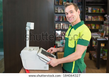 Cashier at cash register in shop or store with books in background - stock photo