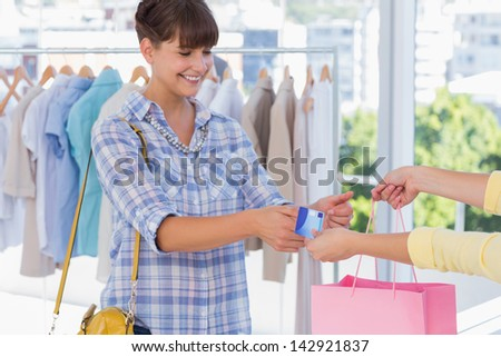 Cashier giving credit card and shopping bag to a smiling customer - stock photo
