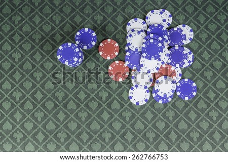 casino background poker chips sitting on green poker felt with room for text - stock photo