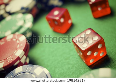 casino chips and dices stacking on a green felt - stock photo
