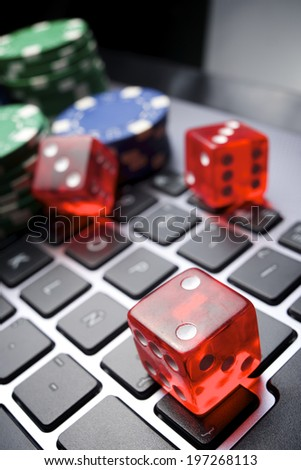 Casino chips, cards and dices stacking on a laptop - stock photo